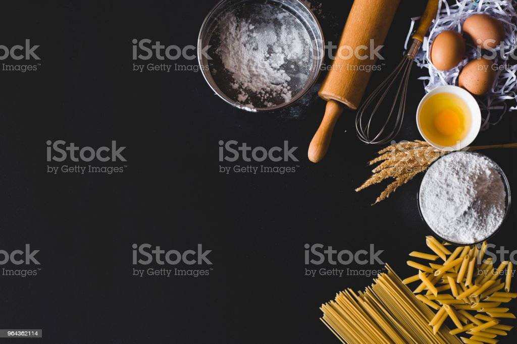 Pasta cooking ingredients on table kitchen table. Top view with space...