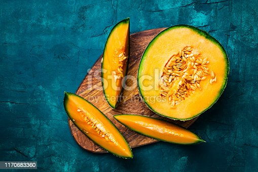 Flat lay food photography of fresh melon slices on a blue green grunge background with copy space. Summer fruit.