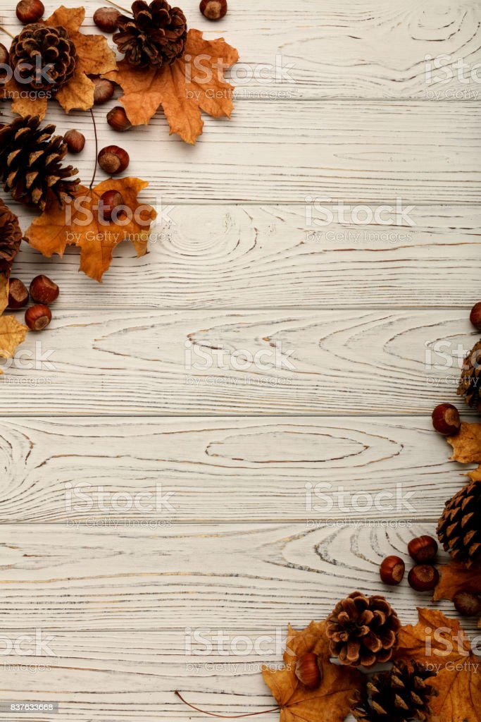 Flat lay frame of autumn leaves, cones and nuts on a wooden background. stock photo