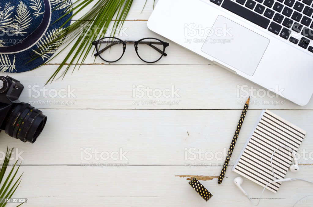 Flat lay photo of office desk with laptop, palm leaf, eyeglasses and...