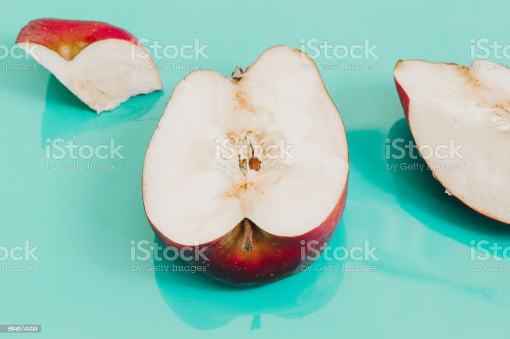 Flat lay fresh half of red apple on turquoise background close up, top view. Minimal fruit royalty-free stock photo