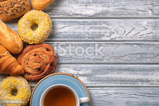 Flat lay fresh sweet pastry and bakery. Sweet yellow donuts with white sprinkles, puff bun with cream and raisins in the shape of a snail, croissants, baguette and cup of tea. Copy space for text.