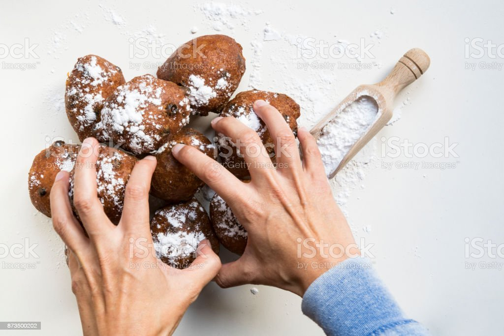 flat lay, greedy hands packing, traditional Dutch oliebollen, oil dumpling or fritter, with wooden spoon, for New Year's Eve_ stock photo