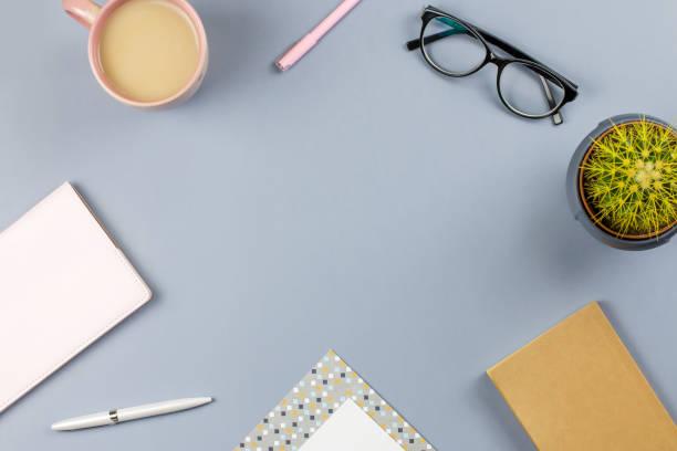 flache laien home-office schreibtisch. weiblichen arbeitsbereich mit brillen, notizbuch, tagebuch, pflanze, tee tasse. textfreiraum - pastellstifte stock-fotos und bilder