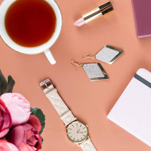 flache laien home-office schreibtisch. weiblichen arbeitsbereich mit notizblock, blumen, tee, schokolade cookies und mode-accessoires. mode und beauty blogger-konzept. - ohrringe rose stock-fotos und bilder
