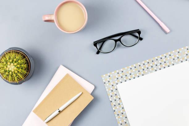 flache laien home-office schreibtisch. weiblichen arbeitsbereich mit brillen, planer, tagebuch, pflanze, tee tasse. textfreiraum - pastellstifte stock-fotos und bilder
