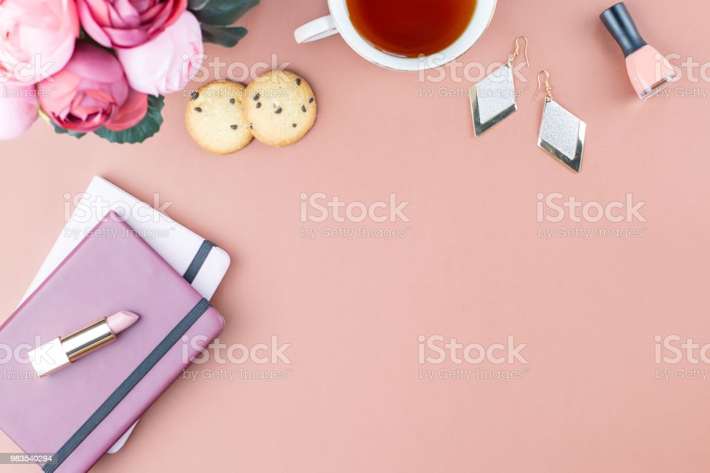 Flat lay home office desk. Feminine workspace with note pad, pink...