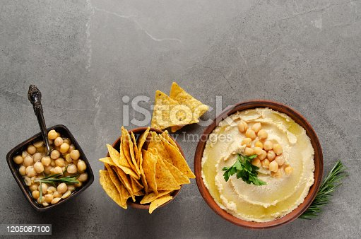 Flat lay Hummus in clay dish topped with chickpeas and green coriander leaves on stone table served with tortilla chips
