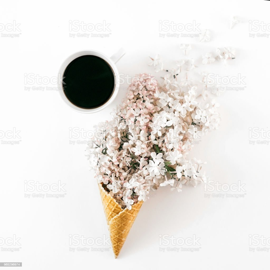 Flat lay ice cream cone with branch white lilacs and cup coffee on white background. Minimal spring concept. Top view zbiór zdjęć royalty-free