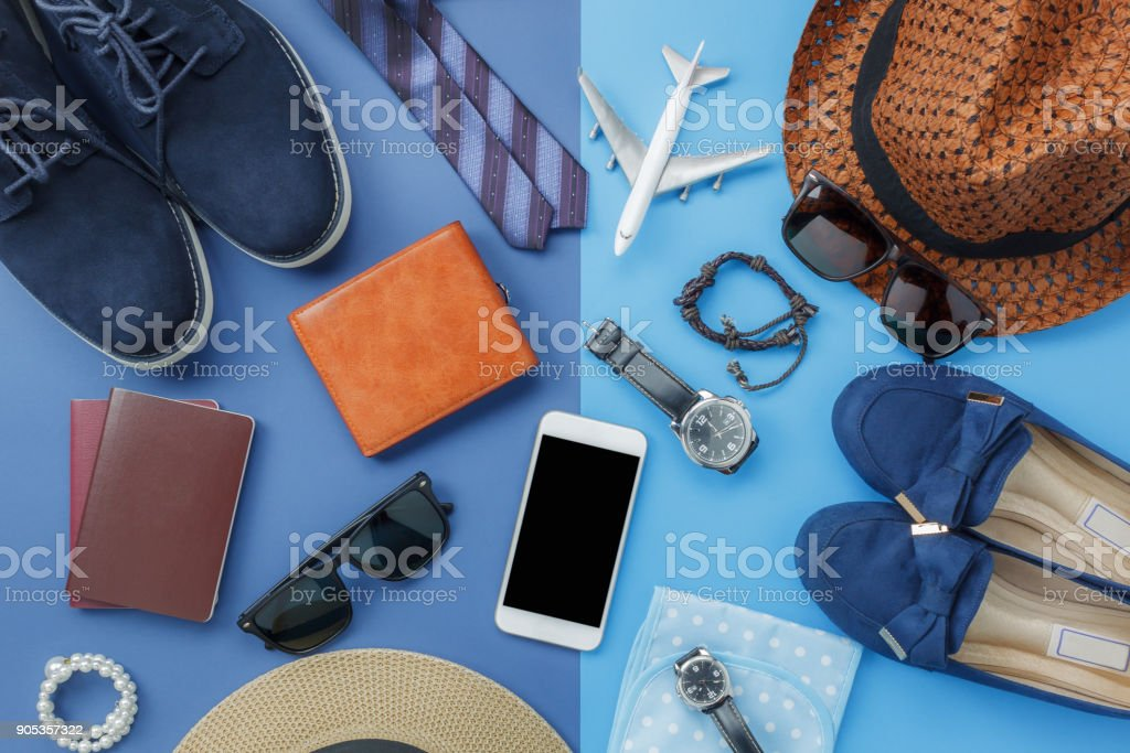 Flat lay image of accessory clothing man or women to plan travel in holiday background concept.Mobile phone & passport with items in vacation season.Table top view object on blue paper.Pastel tone. stock photo
