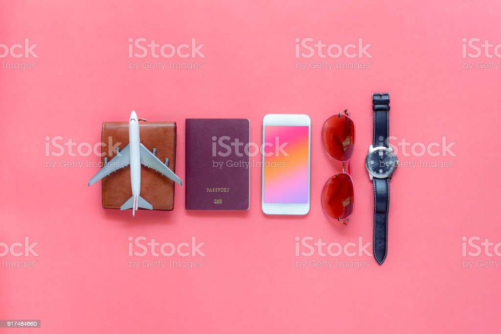 Flat lay image of accessory clothing man or women to plan travel in holiday background concept.Mobile phone & passport with many item in vacation season.Table top view several object on pink paper. stock photo