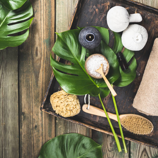 flat lay layout with monstera leaves and cosmetic care products Spa background, flat lay layout with monstera leaves, vintage tray and cosmetic care products spa belgium stock pictures, royalty-free photos & images