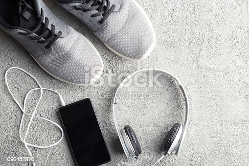 Flat lay lifestyle composition. Sneakers, smartphone and headphones
