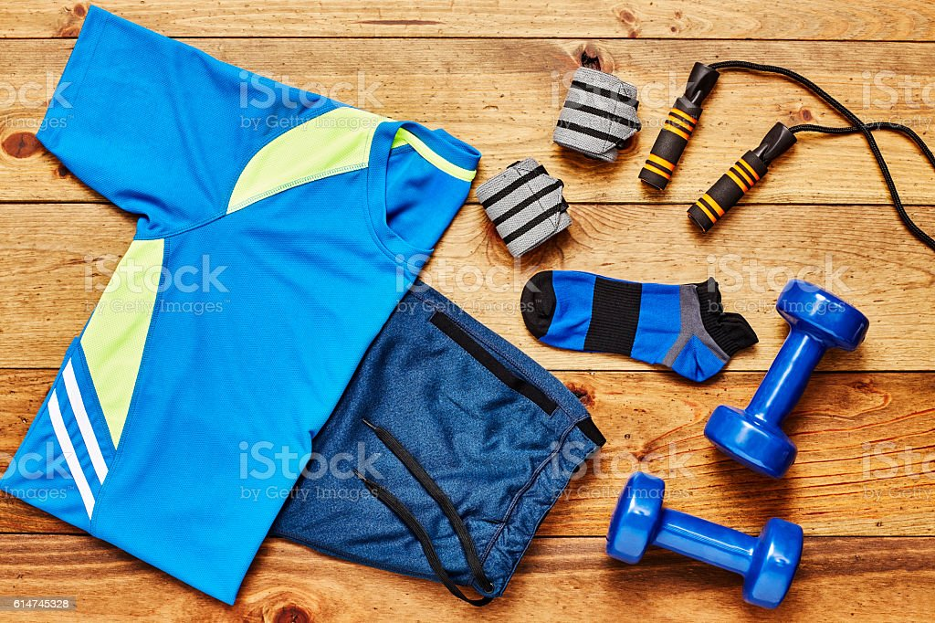 Flat Lay - Men's sportswear with exercise equipment on floor stock photo