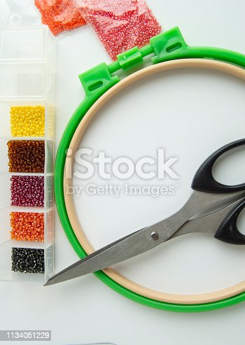 istock Flat lay needlework and embroidery accessories, scissors hoops and beads on white background, vertical frame 1134051229