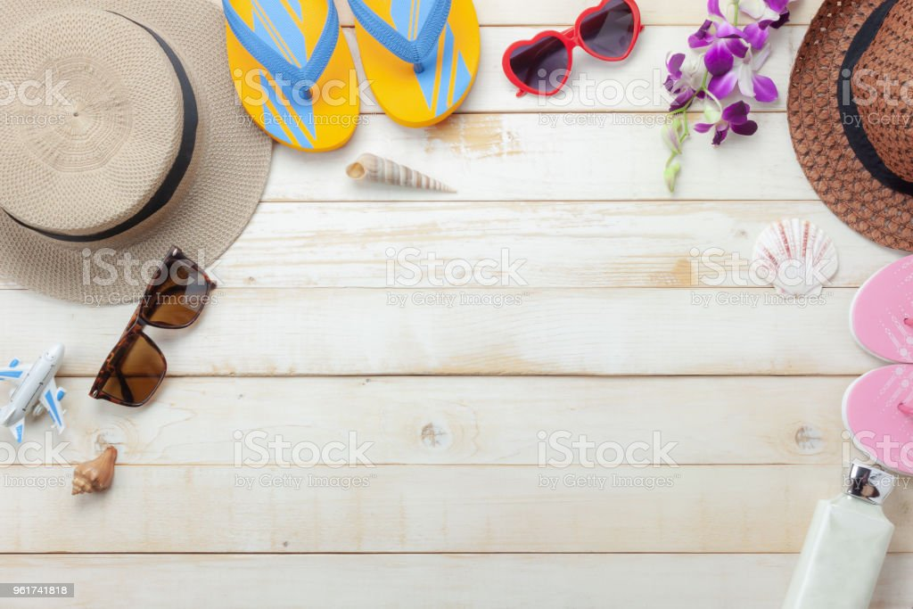 Flat lay objects the accessory for travel summer holiday background concept.Table top view of fashion man & woman clothing to traveler at beach trip on modern rustic white wooden.Copy space design. stock photo