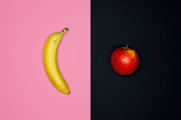 Flat Lay Of A Banana And An Apple. Social Theme Of inequality and discrimination of Gender. stock photo