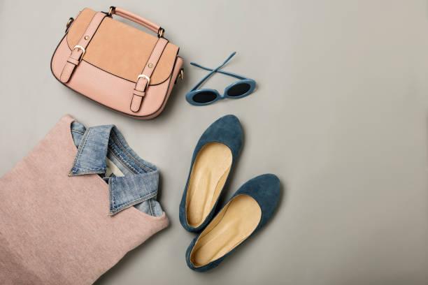 wohnung lag eine lässige frau mode outfit - jeans, rosa kleid, handtasche und sunglsses. draufsicht auf grauem hintergrund. - handtasche jeans stock-fotos und bilder