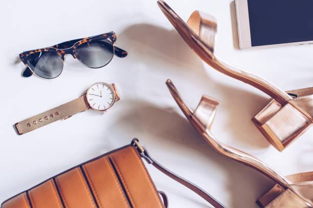 flache lay einen minimalen satz von weiblichen accessoires: goldene armbanduhr mitte heel sandalen mit riemchen, leder schnalle tasche, handy und leopard sonnenbrille - modedetails stock-fotos und bilder