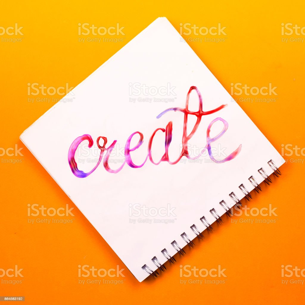 Flat lay of a notebook with colorful hand lettered sign 'Create'. Concept of creativity or education stock photo