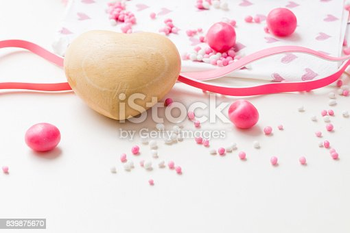 istock flat lay of a wooden heart, pink balls and candy 839875670
