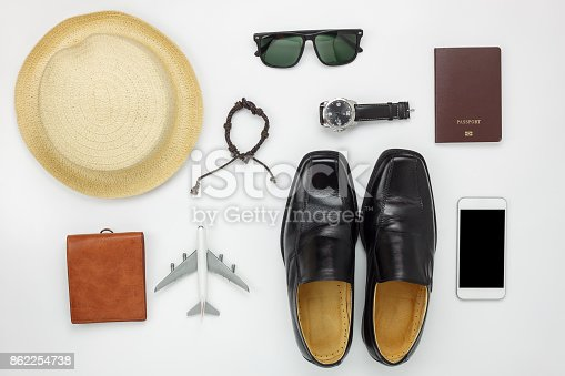 Flat lay of accessories travel and fashion men concept background.Essential items for trip on the white wooden at home office desk.Variety objects for gentlemen adult or teenage and traveler.