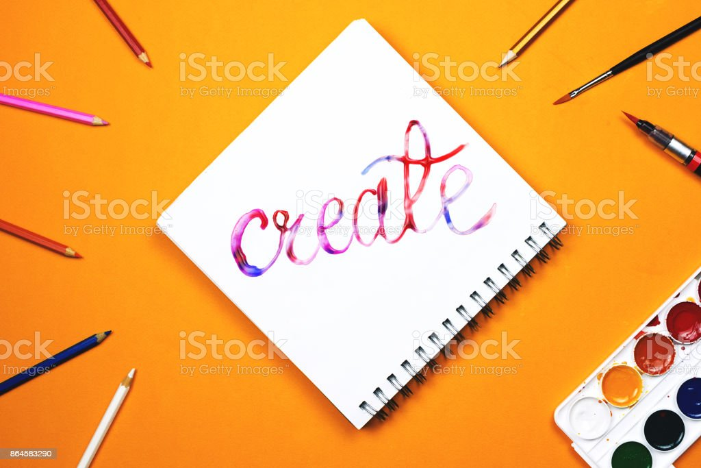 Flat lay of art supplies and notebook with colorful hand lettered sign 'Create'. stock photo