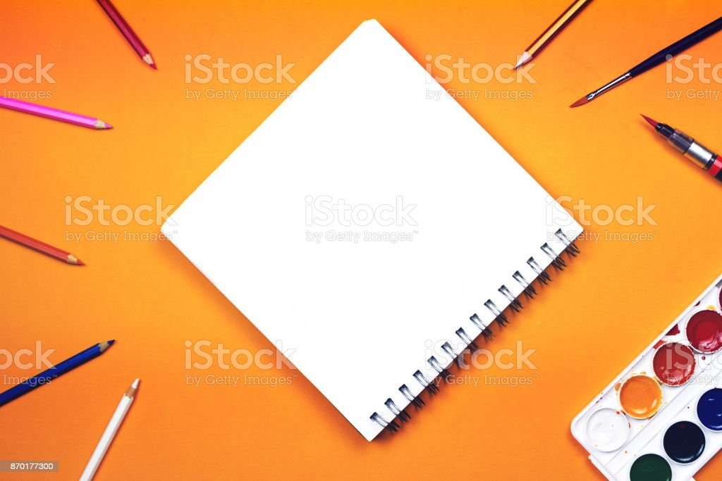 Flat lay of art supplies and notebook with colorful hand lettered sign 'Create' stock photo