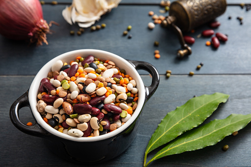 Flat lay of assortment of legumes on black wooden tabletop background, in enamel bowl