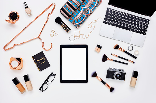 Flat lay of beauty products and accessoroes on bloggers desk