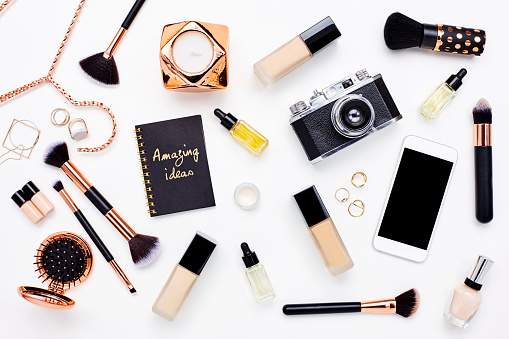 Directly above flat lay shot of smart phone and camera with beauty products. Technologies are with personal accessories on white background. Blank space on mobile phone can be used for advertisement purpose.