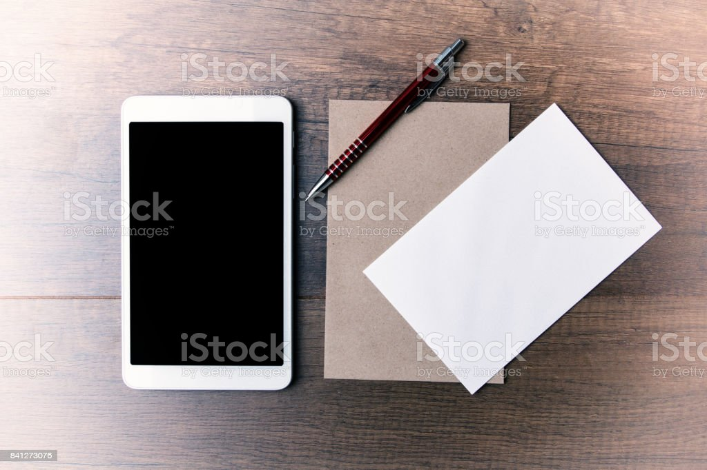 Flat lay of brown envelope with mini ipad stock photo
