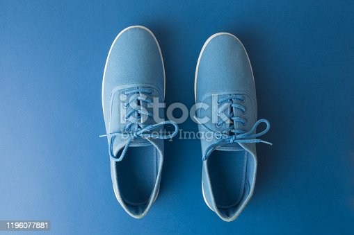 917262406 istock photo Flat lay of canvas sneakers on dark blue background abstract. 1196077881