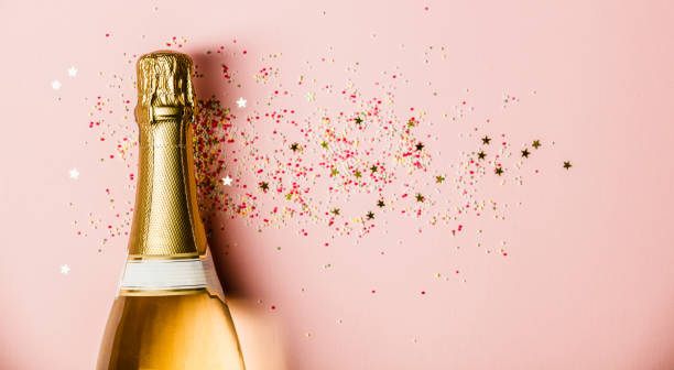 Flat lay of Celebration. Champagne bottle with sprinkles on pink background. stock photo