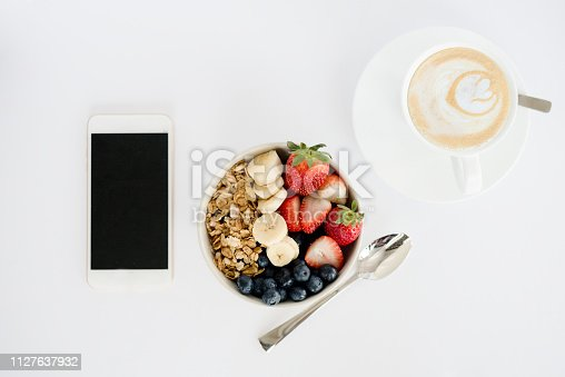 Flat lay of cereal bowl with fruit, coffee and mobile phone over white table background
