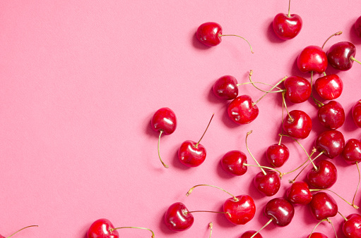 Flat lay of cherries on a pink background. Top view. - Image