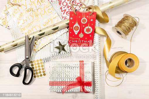 Flat lay of Christmas gifts, decoration paper, ribbons and scissors. Christmas gift concept. Top view