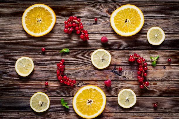 flach zu legen, zitrusfrüchte und rote beeren auf holztisch - küche deko blog stock-fotos und bilder