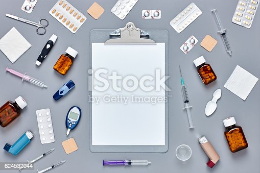 Directly above flat lay shot of clipboard surrounded with medical supplies on gray background with copy space. Medicines are placed with syringes and diagnostic tools. Blank paper can be used for advertisement.