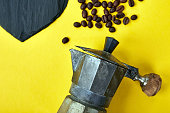 Flat lay of Coffee maker and beans on yellow background. Coffee love concept. Moka coffee pot. Espresso maker. Process of making natural coffee from beans. Top view. Copy space.