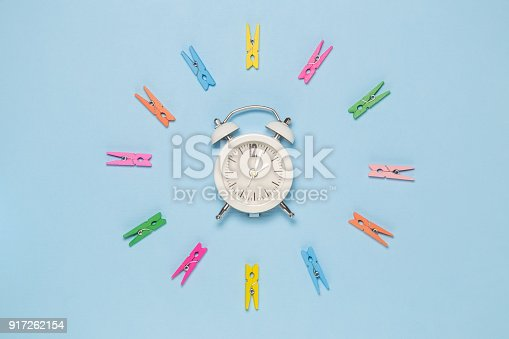 1139289535 istock photo Flat lay of colorful wooden clothes pegs in circle and retro alarm clock on blue background 917262154