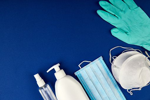 Flat lay of Coronavirus protection, medical protective masks, gloves, hand sanitizer bottles, antiseptic, disinfection, spray on blue background, copy space.