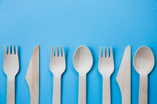 flat lay of different wooden cutlery on blue background - blue table setting stock photos and pictures