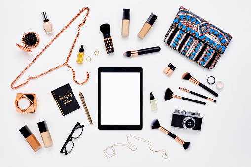Flat lay of digital tablet surrounded by beauty products