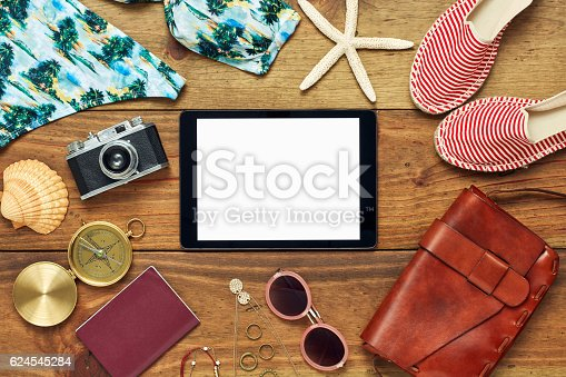941183588 istock photo Flat lay of digital tablet surrounded with beach and travel accessories 624545284