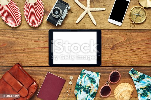 941183588 istock photo Flat lay of digital tablet surrounded with beach travel accessories 624539952