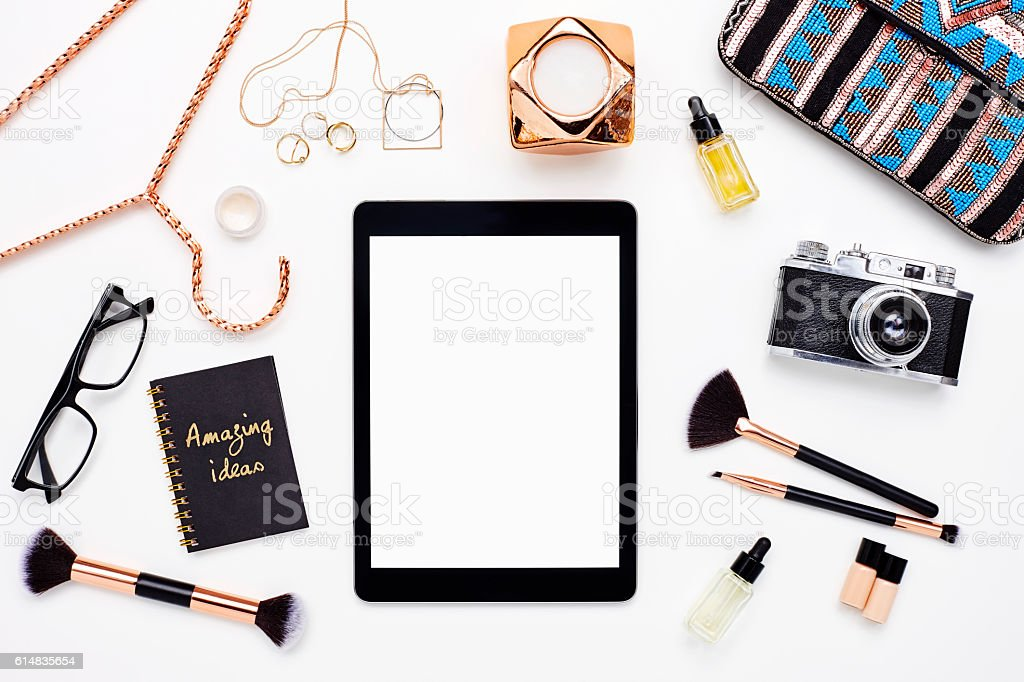 Flat lay of digital tablet surrounded with gold beauty products stock photo