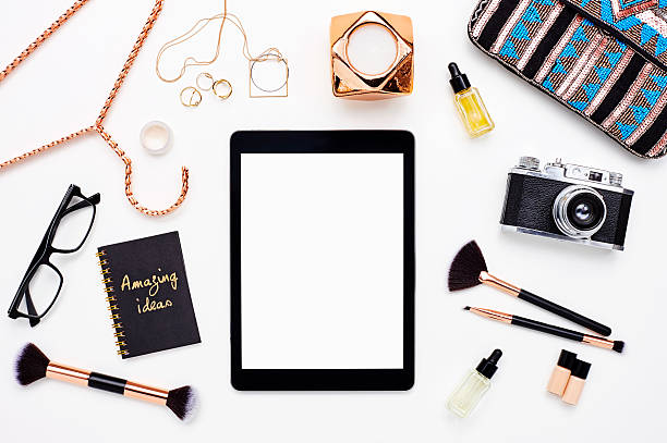 Flat lay of digital tablet surrounded with gold beauty products 스톡 사진