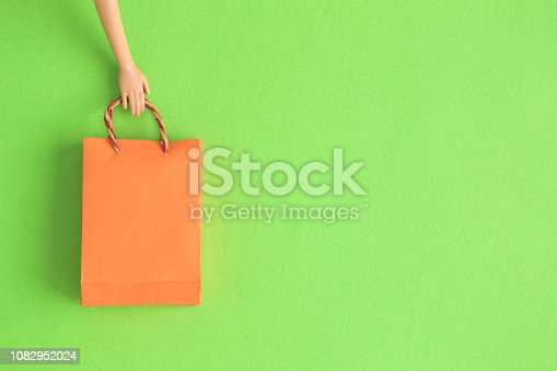 1136804881 istock photo Flat lay of doll hand holding paper shopping bag abstract. Space for copy. 1082952024
