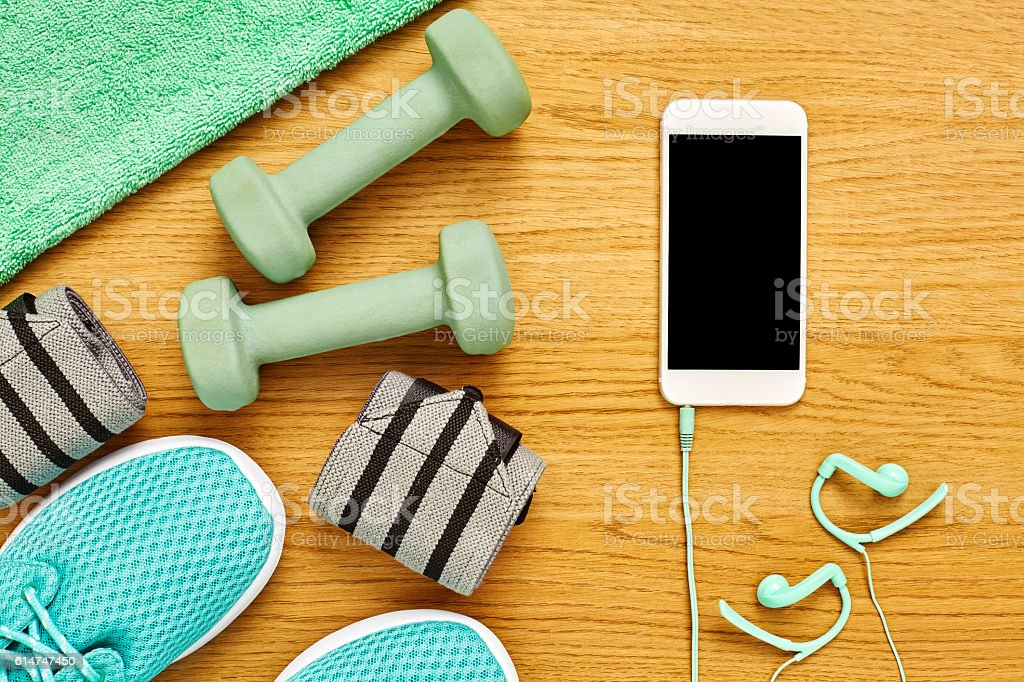 Flat lay of exercise equipment with smart phone on wood stock photo